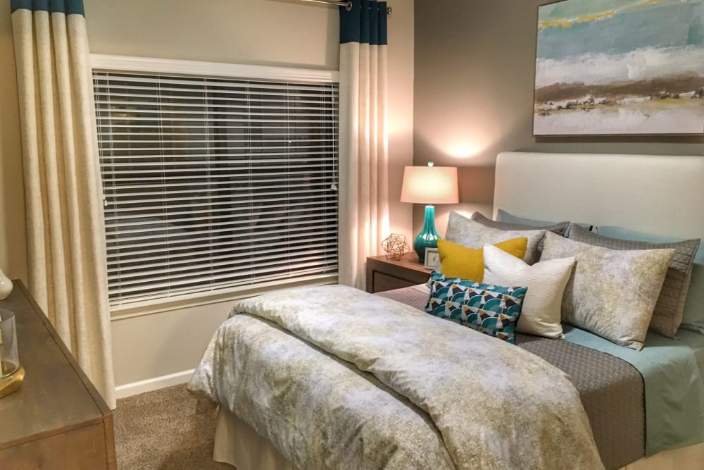 Model home's primary bedroom with an accent wall and draped bay windows at Cahaba Grandview in Birmingham, Alabama