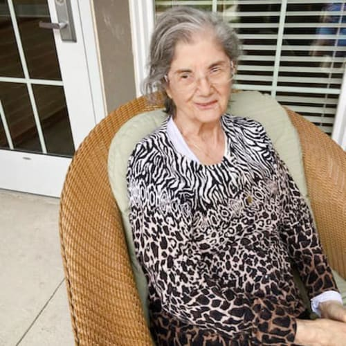 A resident sitting in a wicker chair outside of The Oxford Grand Assisted Living & Memory Care in McKinney, Texas