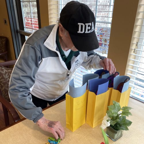 A resident looking through gift bags at Oxford Glen Memory Care at Carrollton in Carrollton, Texas