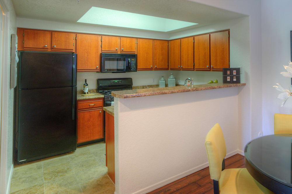 Gourmet kitchen with granite countertops in model home at San Prado in Glendale, Arizona