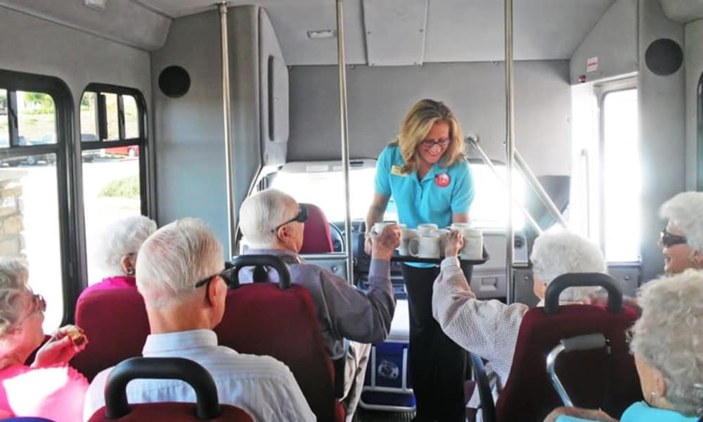 A staff member form Carolina Estates in Greensboro, North Carolina handing out mugs on the community bus
