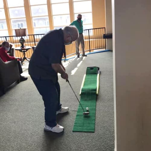 Resident playing indoor minigolf at The Oxford Grand Assisted Living & Memory Care in McKinney, Texas