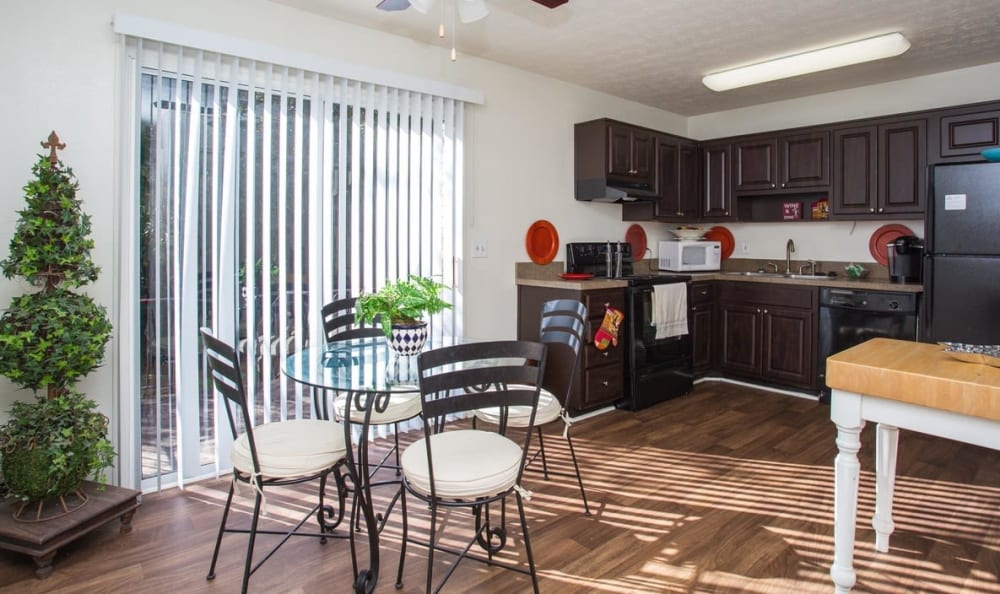 View of the modern kitchen with sleek black appliances from the dining area of a model home at The Arbors at Smyrna in Smyrna, Georgia