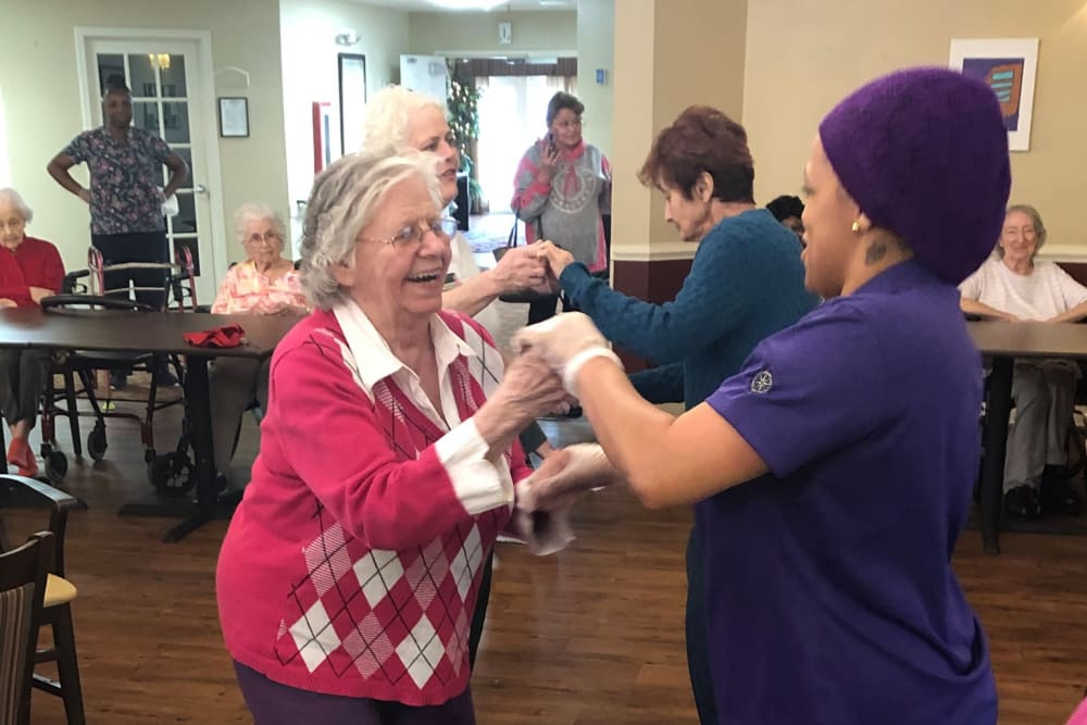 A resident and a staff member happily dancing at Magnolias of Chesterfield in Chester, Virginia