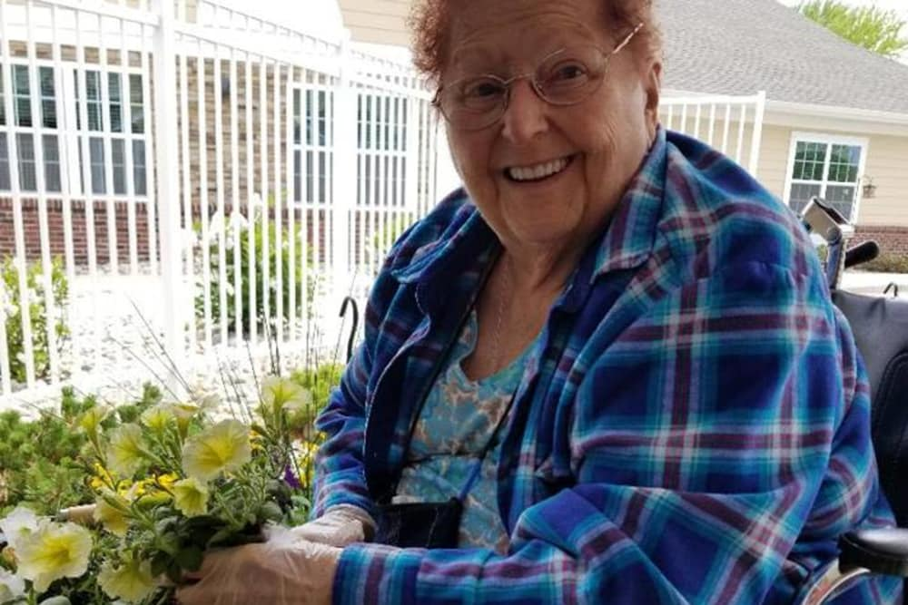A happy resident planting flowers at The Willows at Howell in Howell, Michigan