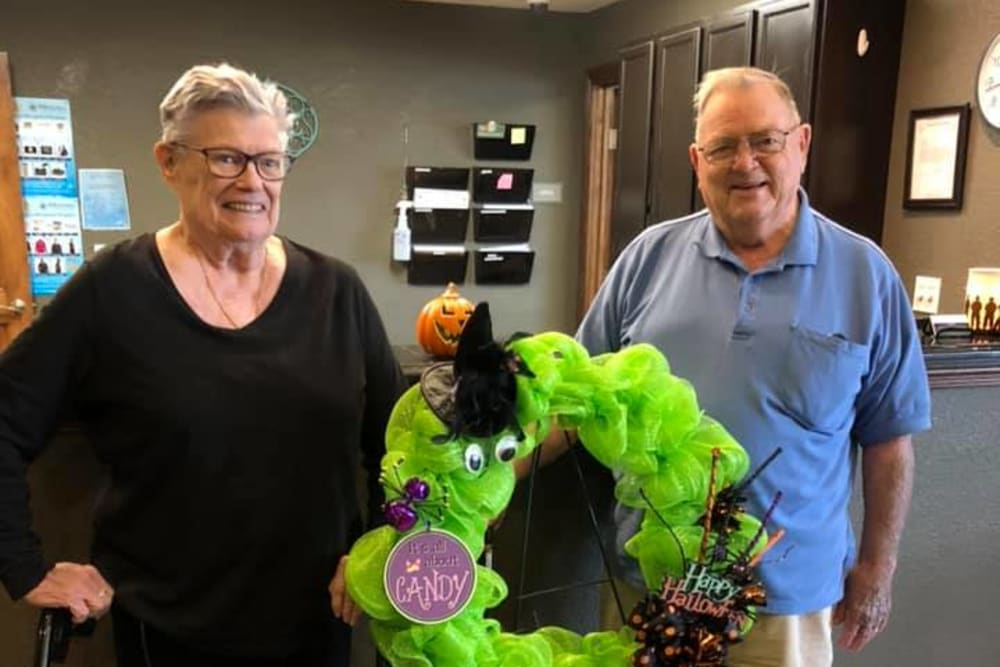 Residents standing by a fun Halloween wreath at Villas of Holly Brook Chatham in Chatham, Illinois