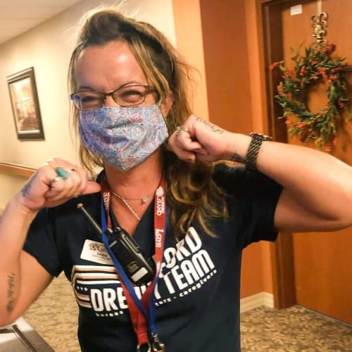 An excited masked caretaker at The Oxford Grand Assisted Living & Memory Care in Wichita, Kansas