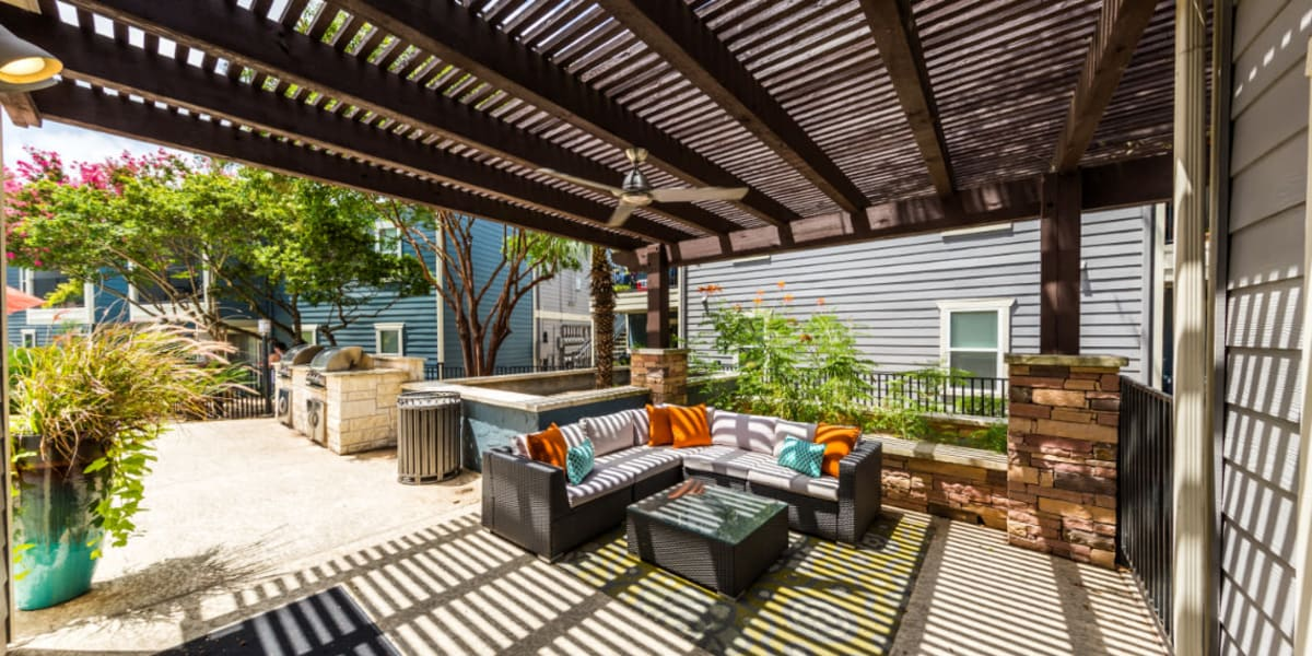 BBQ and gazebo area with cushioned couches at Austin Midtown in Austin, Texas