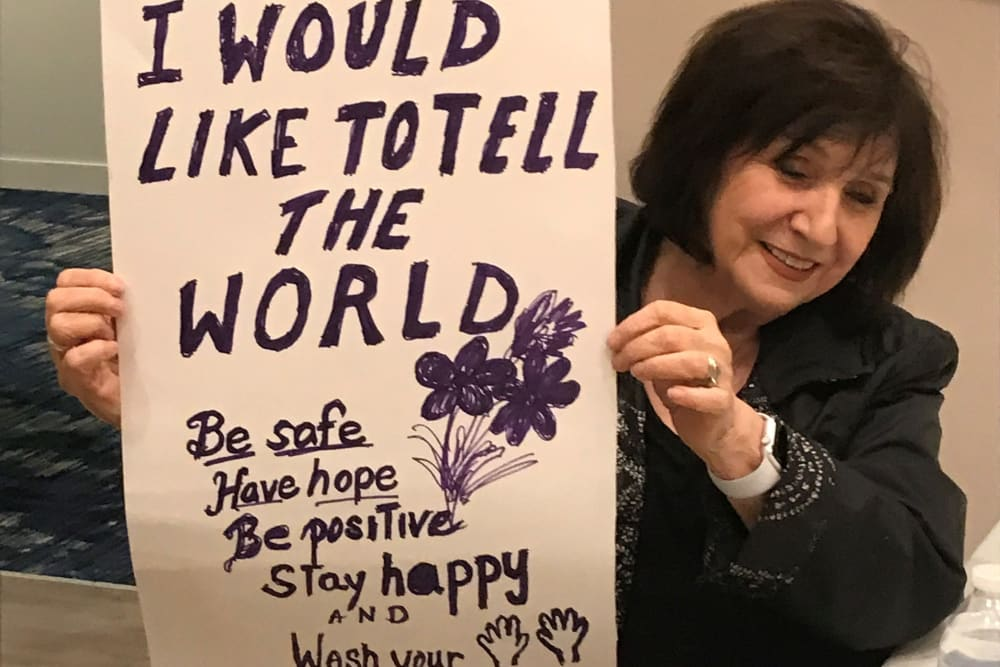 Clearwater resident holds up a positive message sign she created