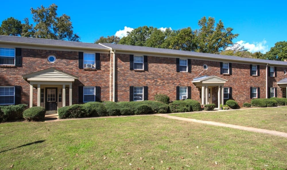 Exterior view of resident buildings and well-managed landscaping at The Arbors at Smyrna in Smyrna, Georgia