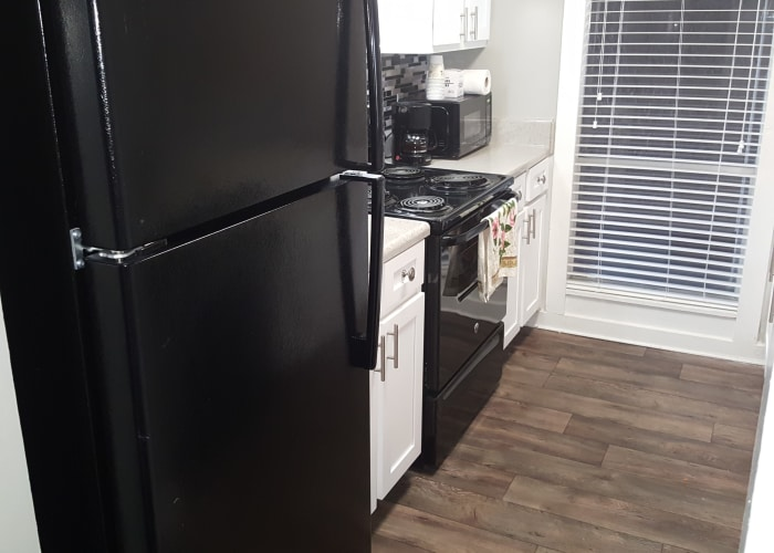 Fully equipped kitchen with black appliances & hardwood-style flooring at Pier 5350 in Jacksonville, Florida