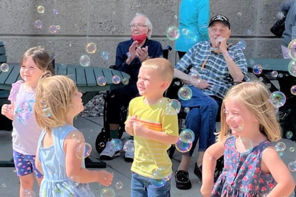 Residents watch as children play with bubbles on a sunny day in Burnsville, Minnesota