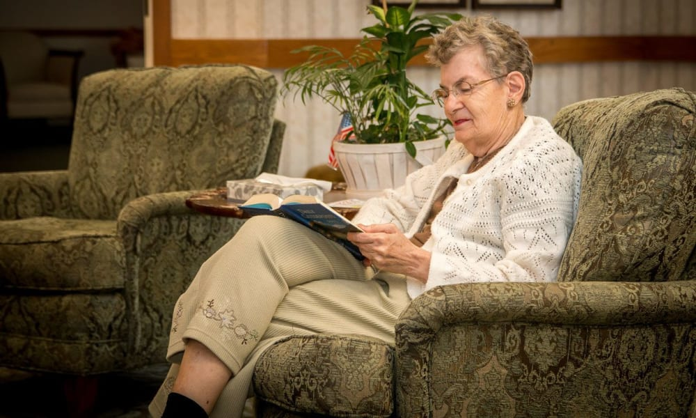 Resident sitting in a lounge chair reading a book at Villa at the Lake in Conneaut, Ohio