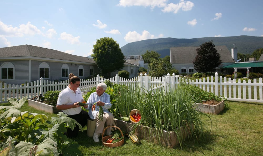 Resident and staff enjoying the community garden at Equinox Terrace in Manchester Center, Vermont