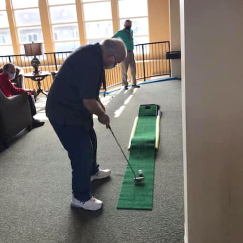 Resident playing minigolf at The Oxford Grand Assisted Living & Memory Care in McKinney, Texas