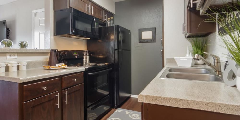 Kitchen with black appliances and dark wood cabinets for a lovely look at The Landings at Steeplechase in Houston, Texas