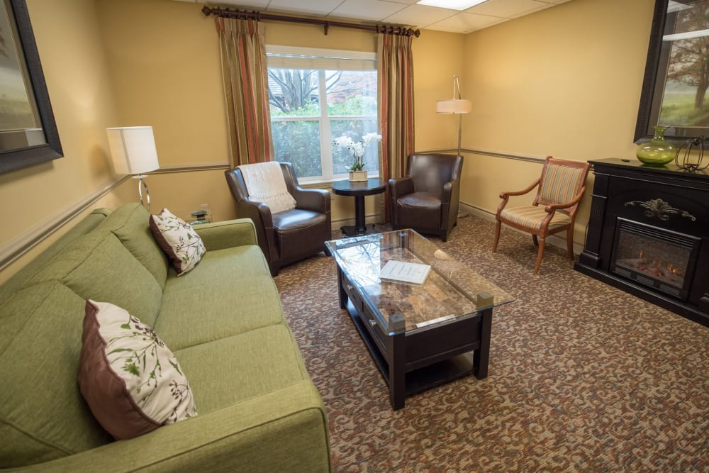 Community lounge area with cozy couch and fireplace at Kenmore Senior Living in Kenmore, Washington