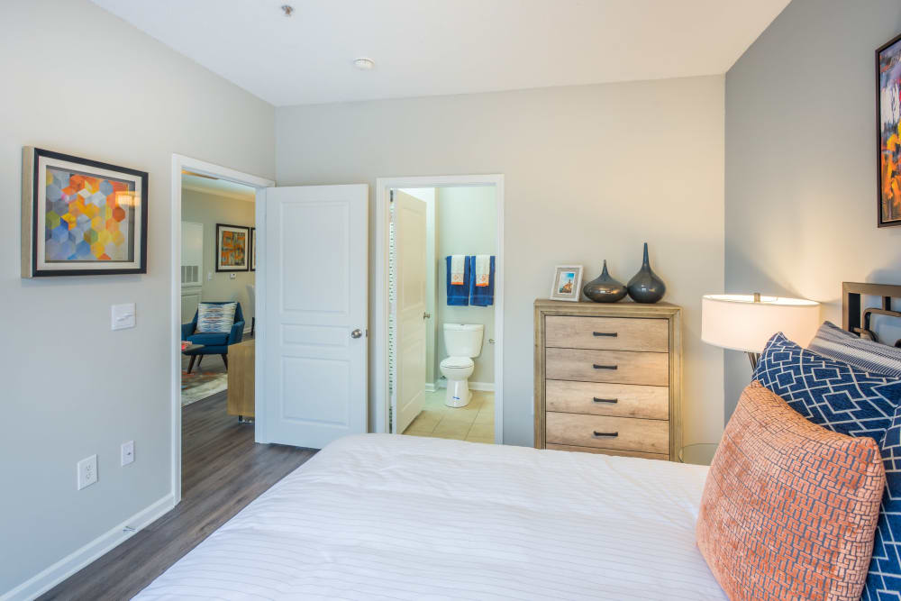 Model apartment's primary bedroom with hardwood style flooring at The Avant at Steele Creek in Charlotte, North Carolina