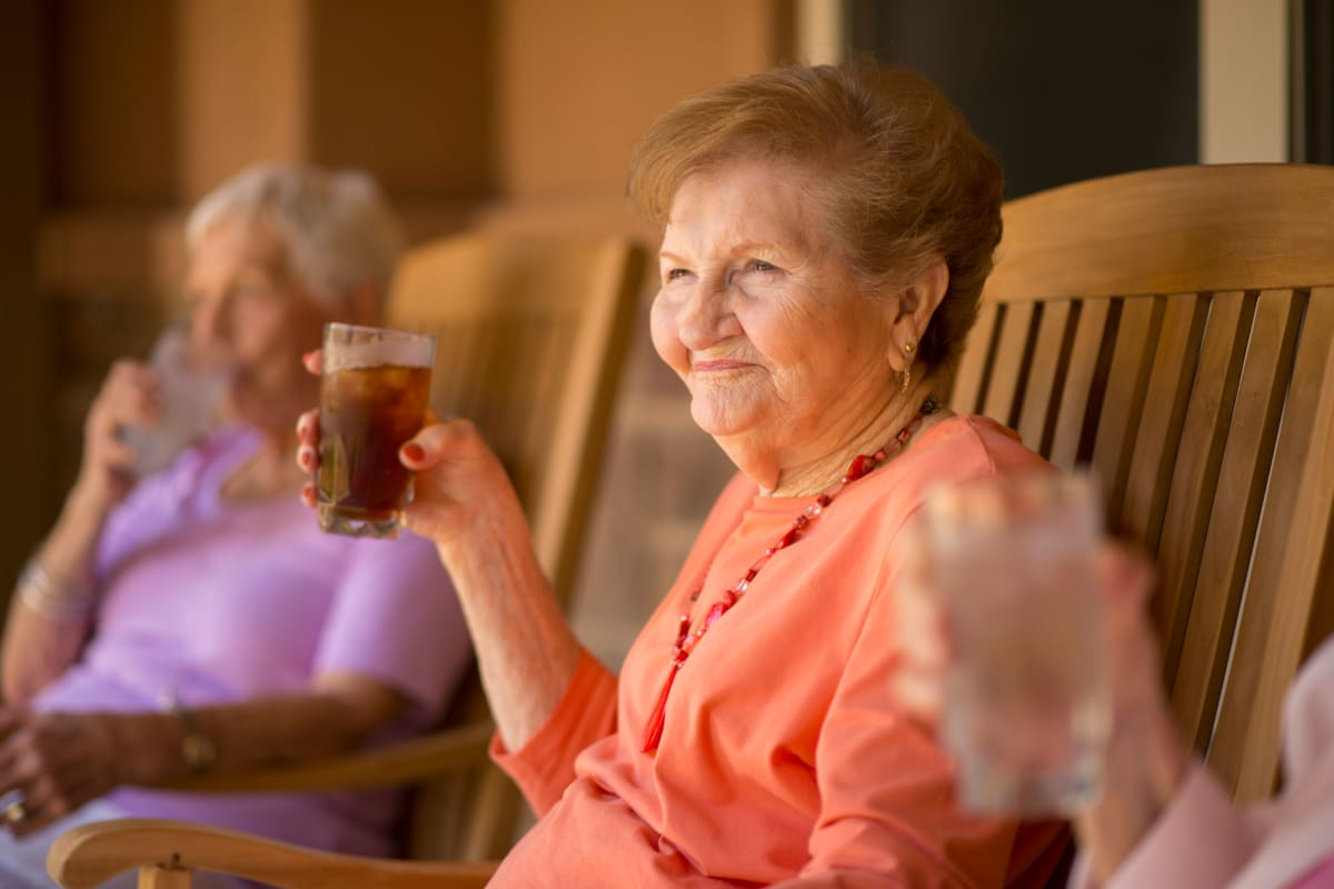 A lady sitting in the sun having a drink at Watercrest at Kingwood in Kingwood, Texas