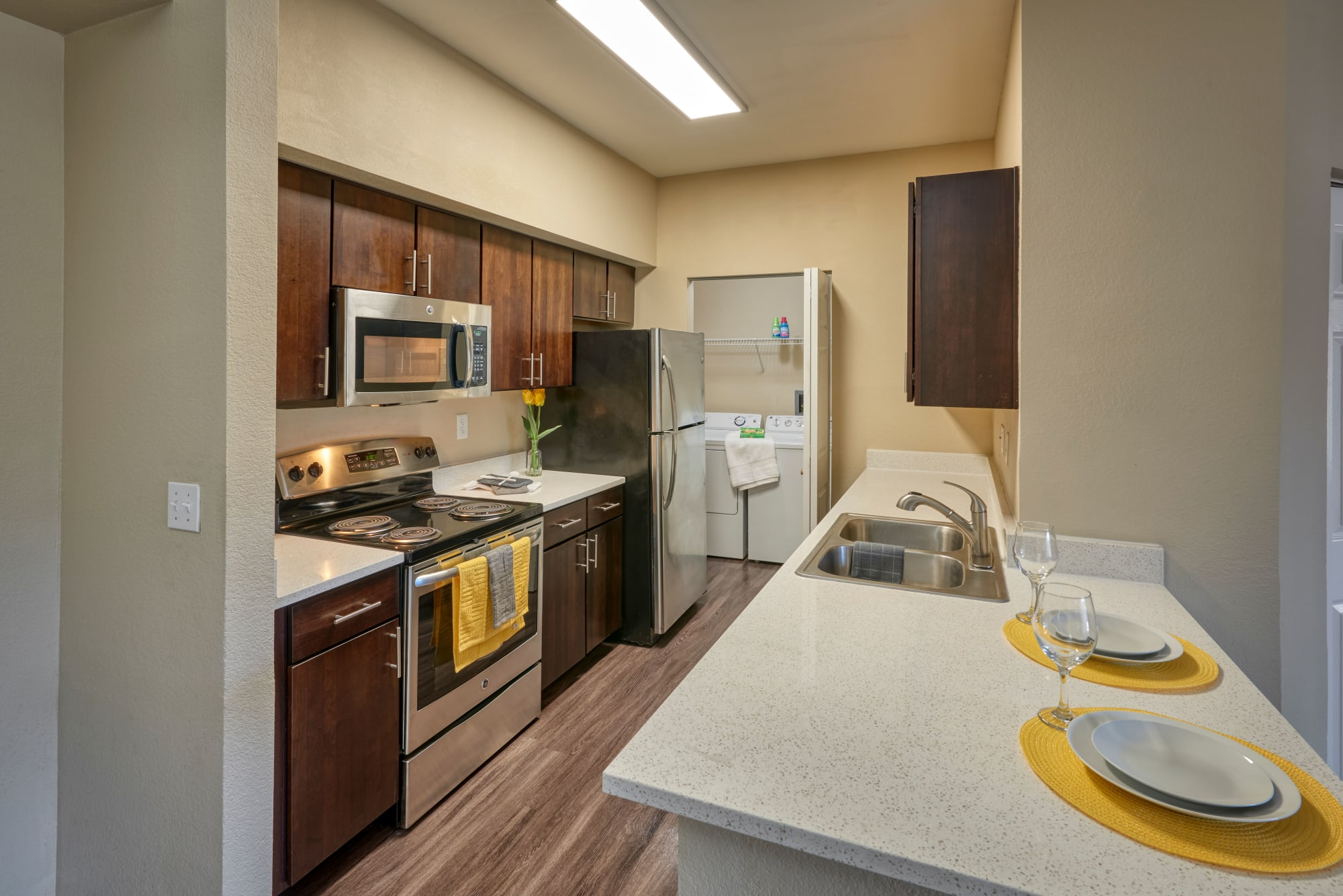 A renovated kitchen with brown cabinets and a breakfast bar at The Crossings at Bear Creek Apartments in Lakewood, Colorado
