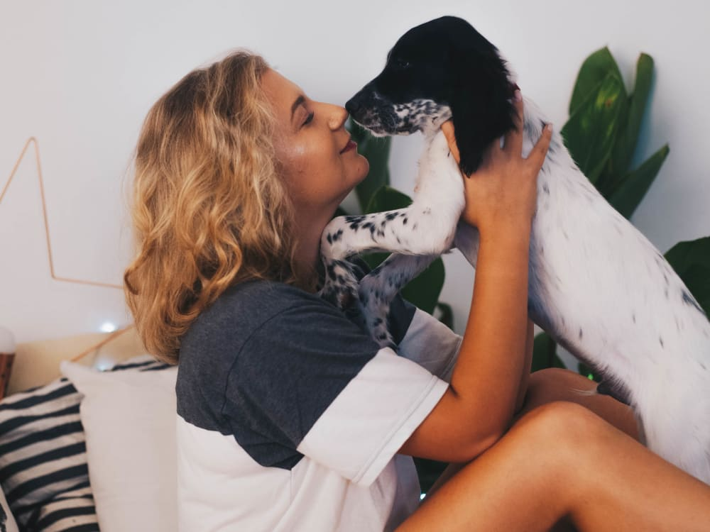 Resident giving her puppy a kiss in their new home at Sofi at Topanga Canyon in Chatsworth, California