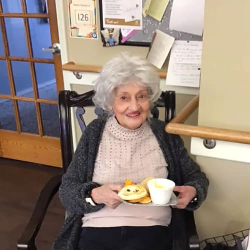 A resident sitting with a breakfast plate at Canoe Brook Assisted Living & Memory Care in Catoosa, Oklahoma