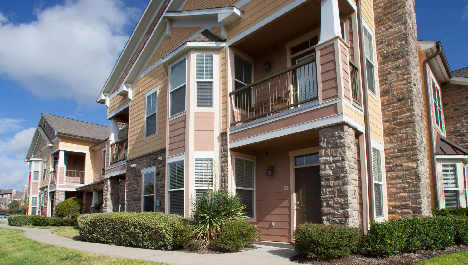 Resident buildings surrounded by professionally maintained landscaping at Olympus Katy Ranch in Katy, Texas