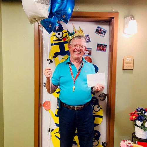 Happy resident standing outside his apartment holding balloons and a birthday card at The Oxford Grand Assisted Living & Memory Care in McKinney, Texas