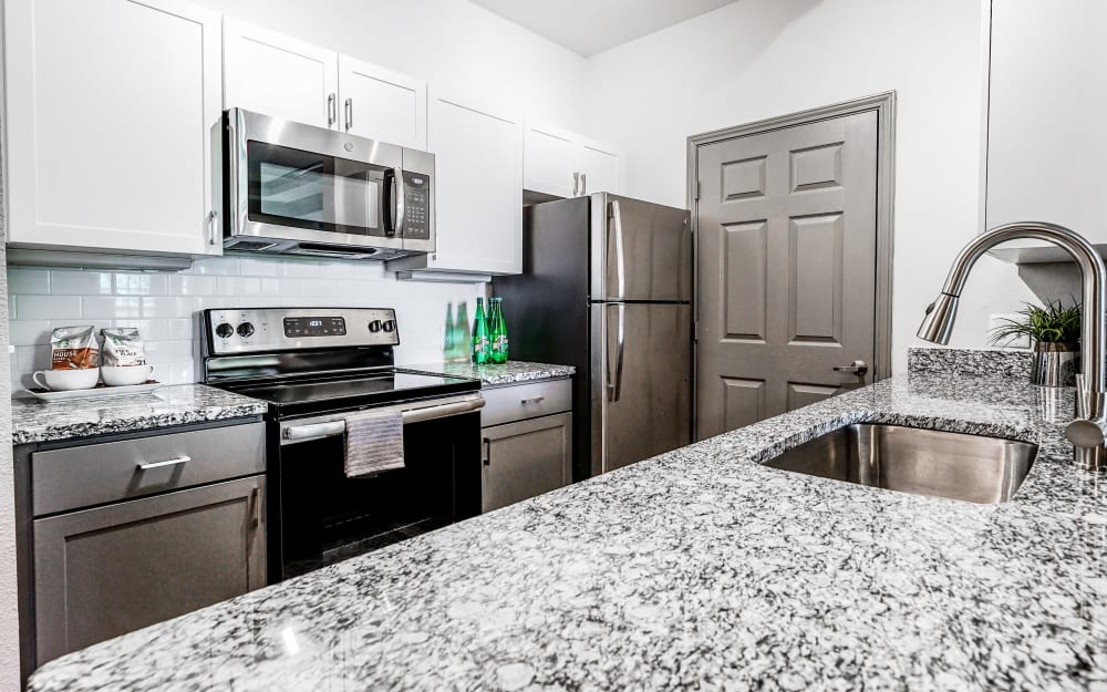 Granite countertops and tile backsplash in model home's kitchen at Beck at Wells Branch in Austin, Texas