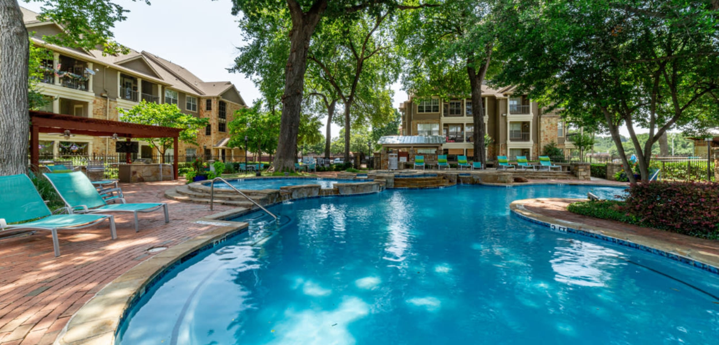 Resort style pool surrounded by lounge chairs at Marquis at Bellaire Ranch in Fort Worth, Texas