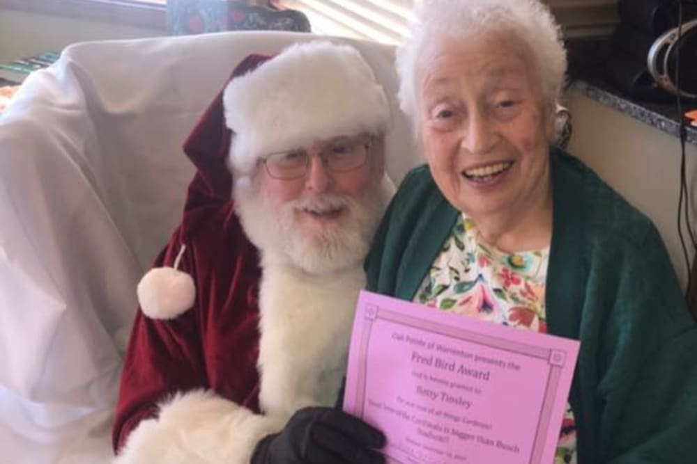 A resident vising with Santa at Oak Pointe of Warrenton in Warrenton, Missouri