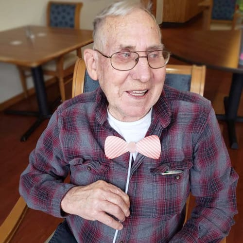 A resident holding a prop bowtie up to his neck at Alderbrook Village in Arkansas City, Kansas