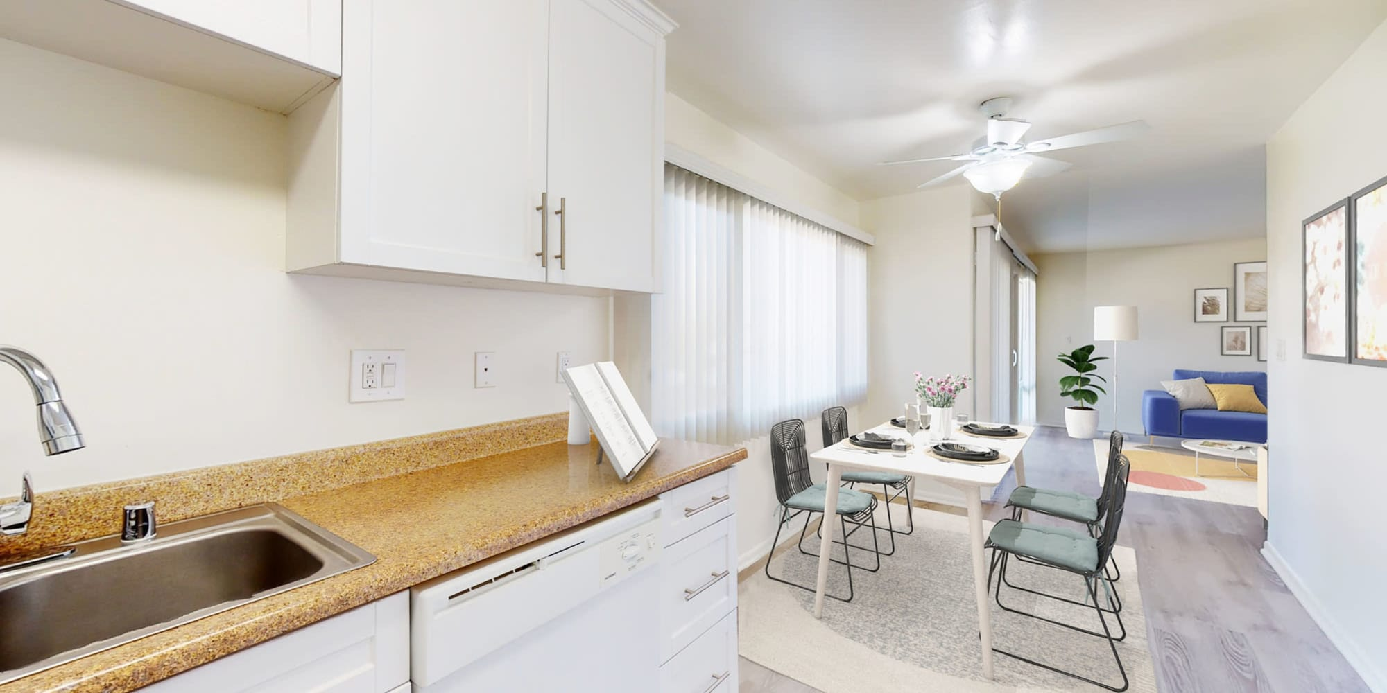 Two bedroom home's open-concept kitchen with white cabinetry looking into the dining area at West Park Village in Los Angeles, California