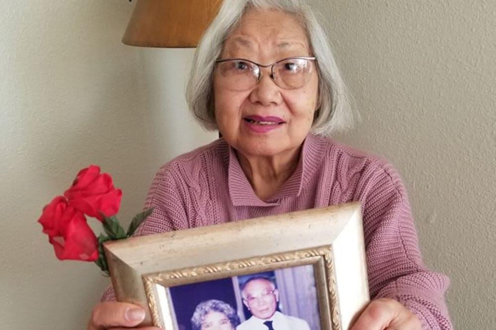 A resident holding a photo at Legacy Oaks of Sacramento in Sacramento, California