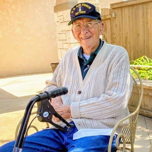 Residing veteran sitting outside at Glen Carr House Memory Care in Derby, Kansas