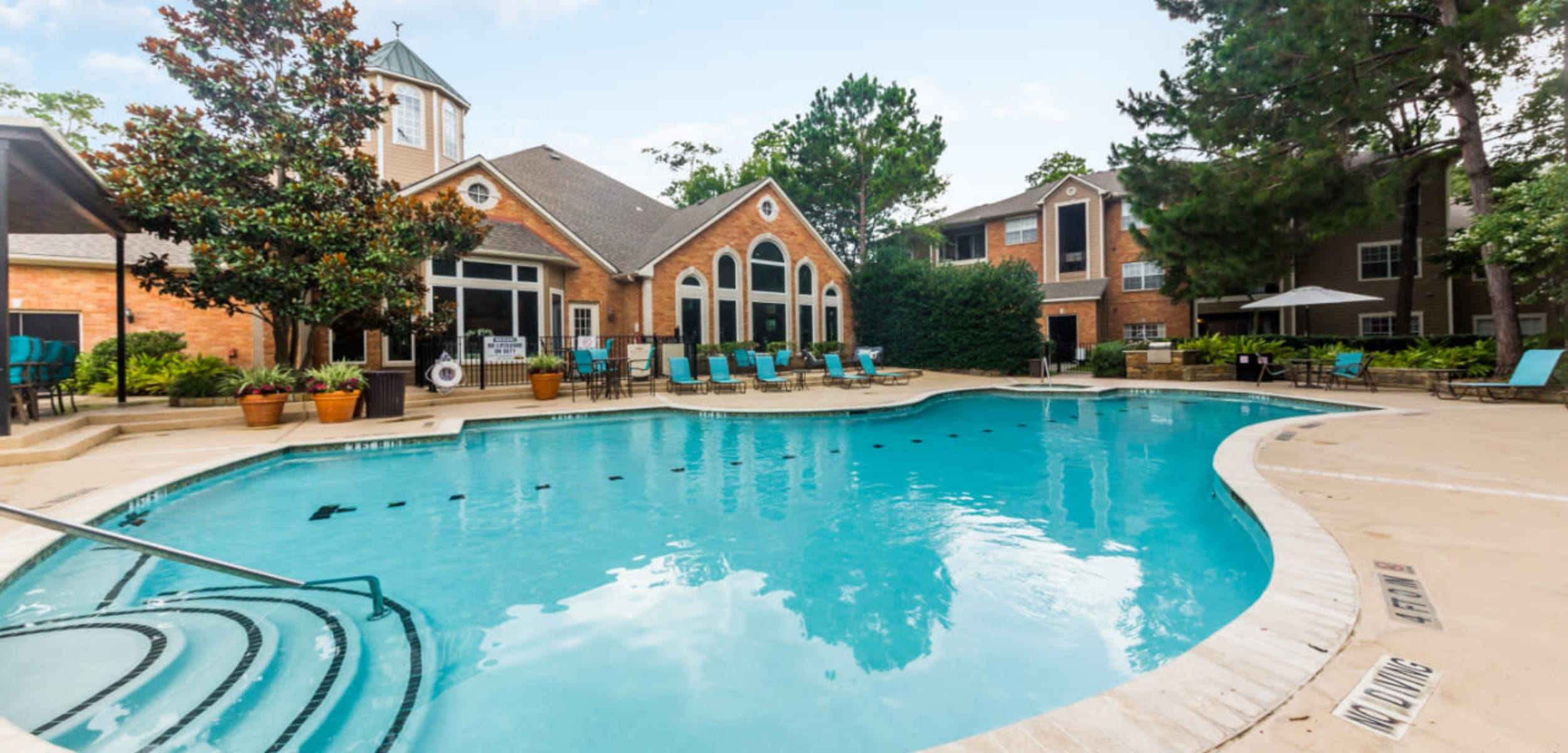 Steps into pool surrounded by lounge chairs at Marquis at Kingwood in Kingwood Texas,