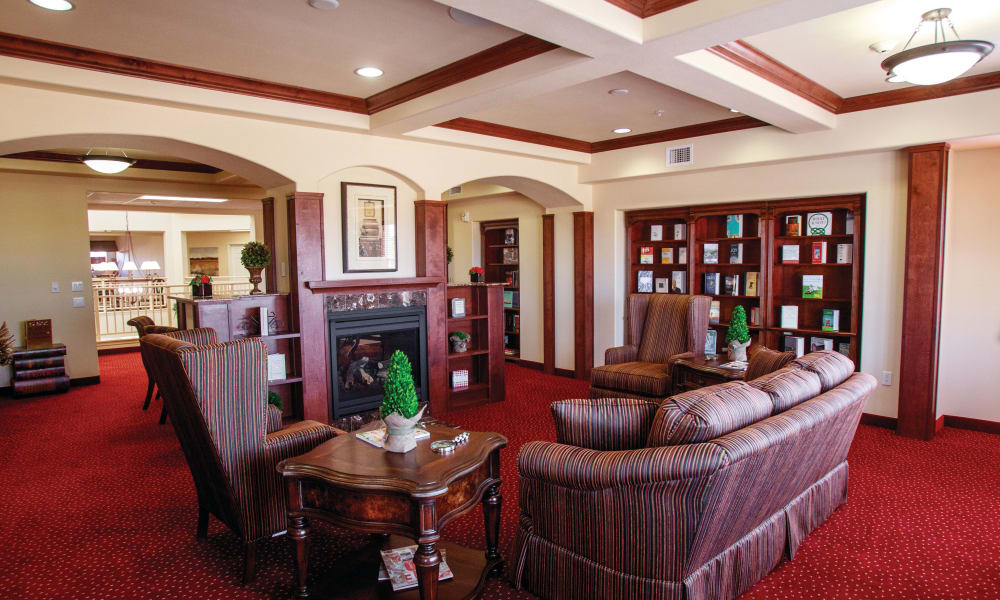 Comfortable fireside seating in the library at Alexis Estates Gracious Retirement Living in Allen, Texas