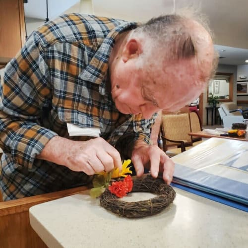 A resident making a wreath at Glen Carr House Memory Care in Derby, Kansas
