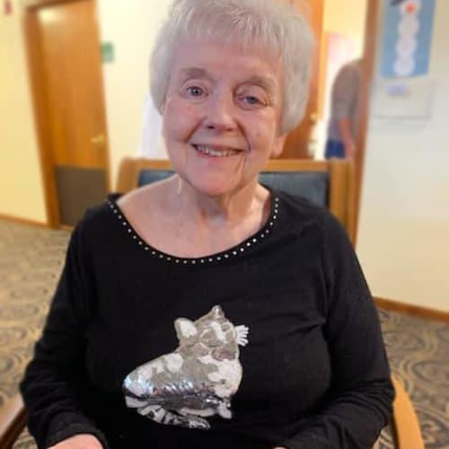 A happy resident wearing a cat themed shirt at Alderbrook Village in Arkansas City, Kansas