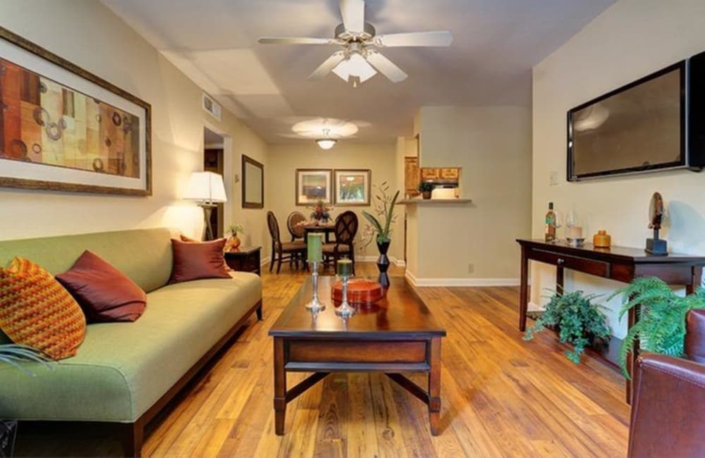 Spacious living area with hardwood floors and ceiling fan in open-concept floor plan of model home at Allegro on Bell in Antioch, Tennessee