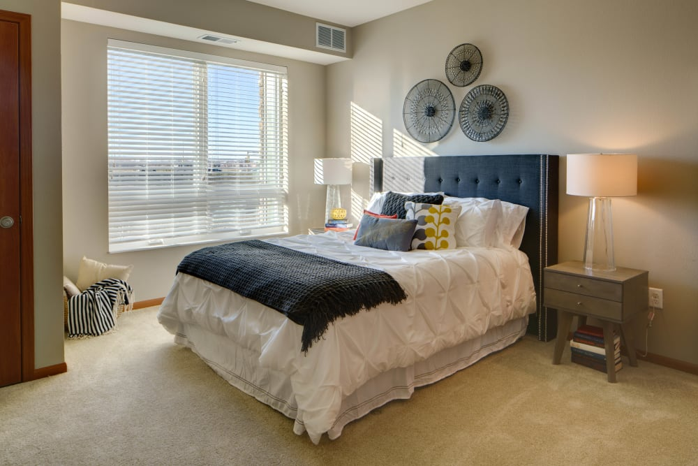 Spacious main bedroom with a large window for natural lighting at Remington Cove Apartments in Apple Valley, Minnesota