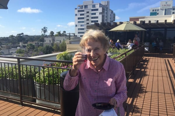 Resident enjoying a patio at Merrill Gardens at Bankers Hill in San Diego, California.