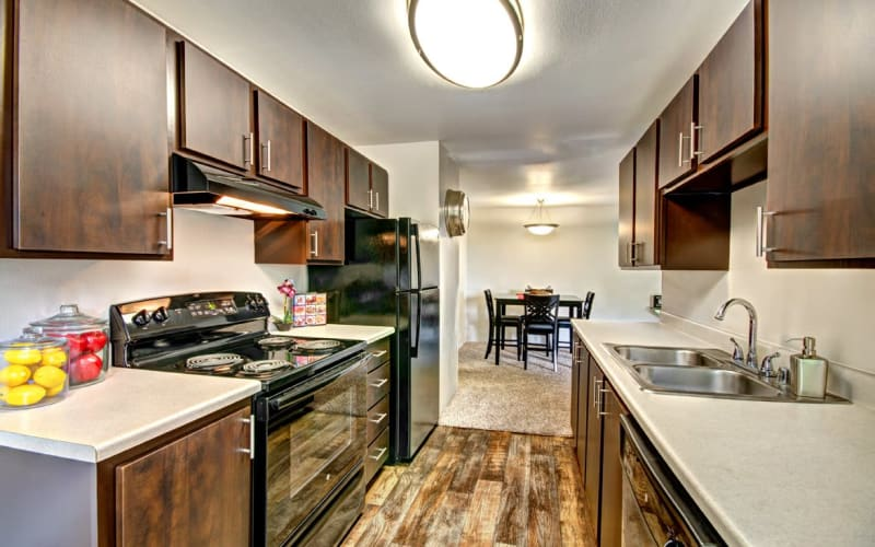 Renovated kitchen with brown cabinets at Wellington Apartment Homes in Silverdale, Washington