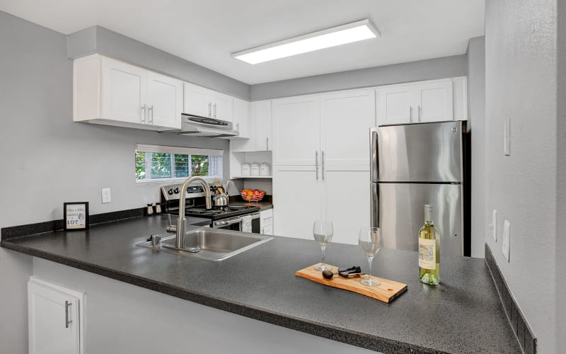 Renovated kitchen with white cabinets at Park South Apartments in Seattle, Washington