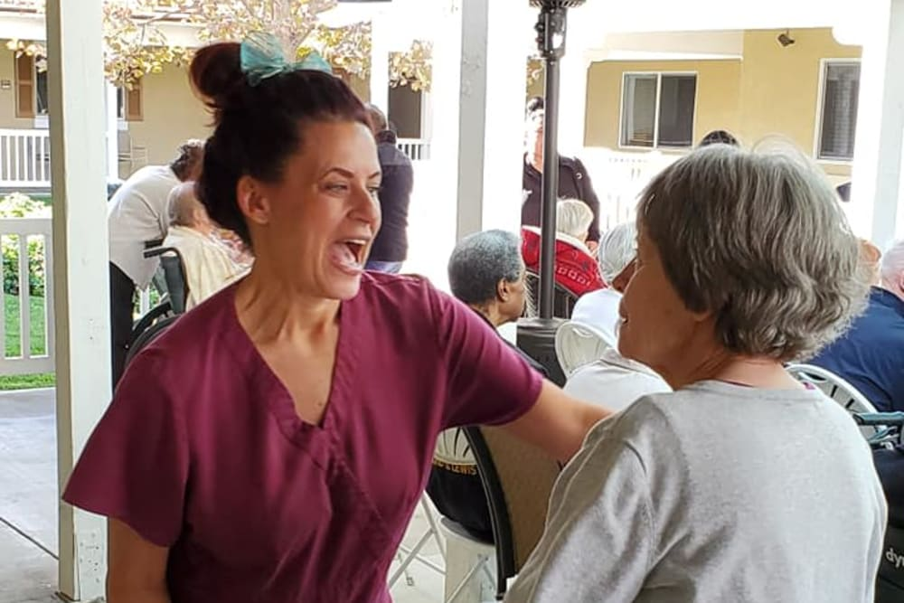 A resident and a staff member having fun at Sunlit Gardens in Alta Loma, California