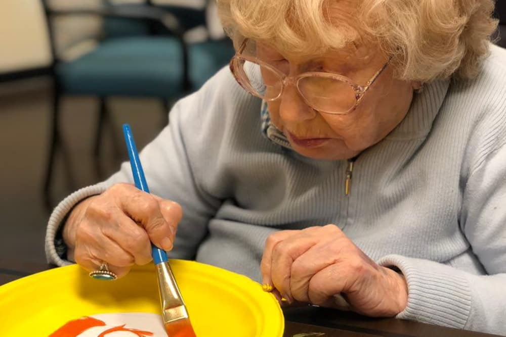 A resident painting on a plate at The Oaks at Northpointe in Zanesville, Ohio