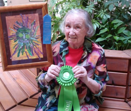 A happy resident poses with her award-winning painting at Arbors Memory Care in Sparks, Nevada