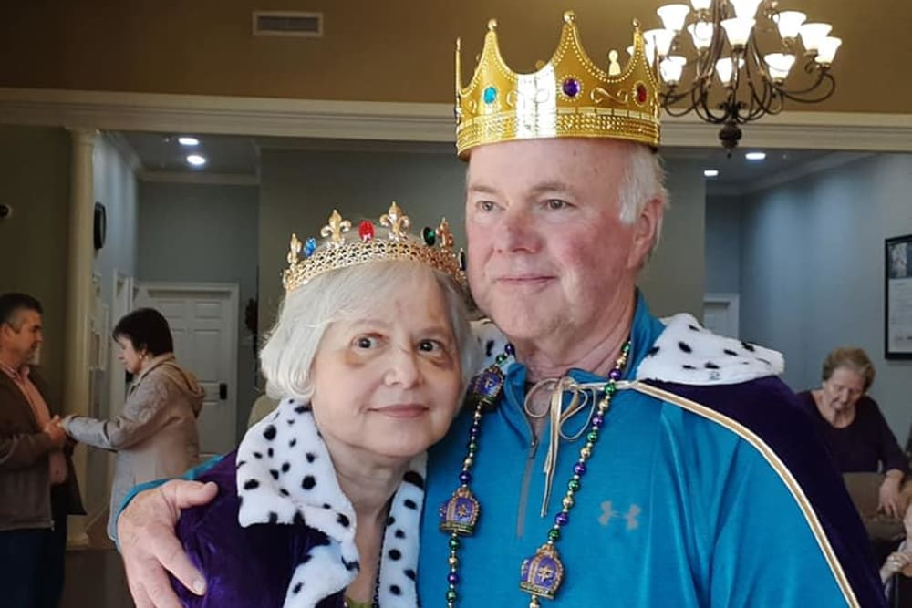 A happy couple dressed as a king and a queen at Cedar Crest Memory Care in Lafayette, Louisiana