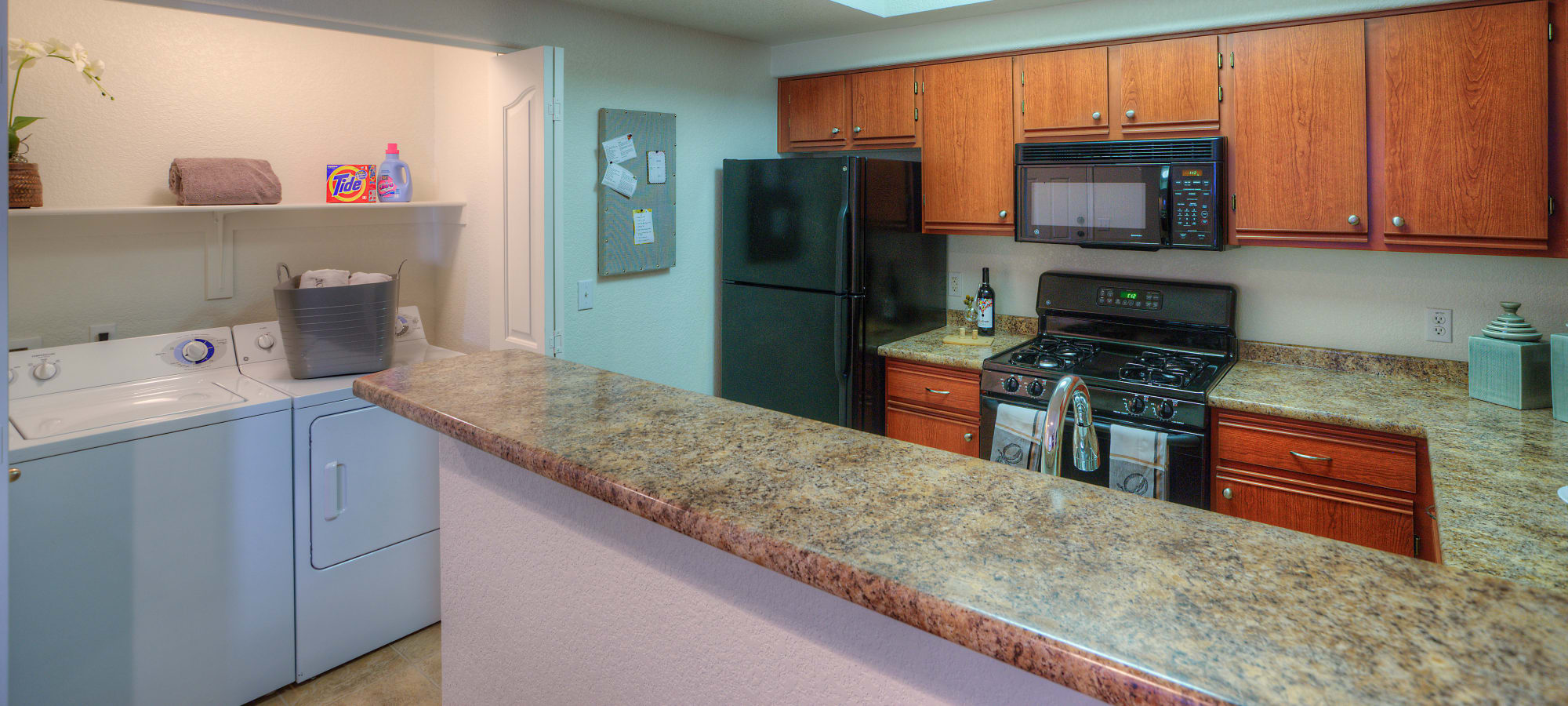 Kitchen with wooden cabinetry next to in-home washer/dryer at San Prado in Glendale, Arizona