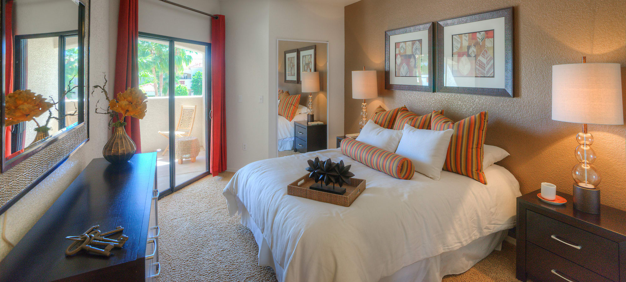 Model bedroom with sliding glass door leading to private patio at San Prado in Glendale, Arizona